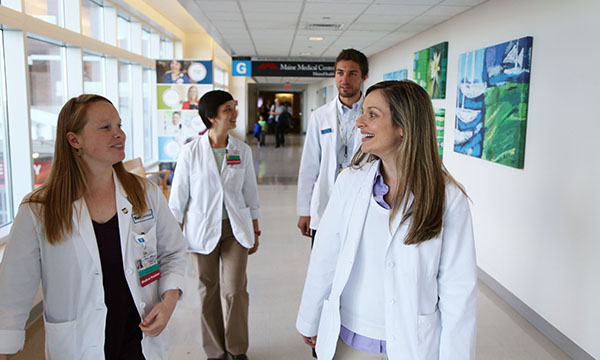 a group of medical providers walking and talking together in a hospital hallway
