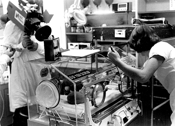 A man filming a NICU nurse with a patient in 1974
